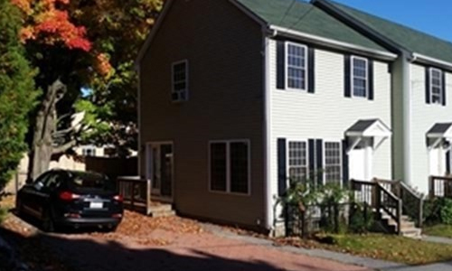 Two bedroom Townhouse for rent in Reading, MA - exterior of home shown - light colored end unit with black shutters