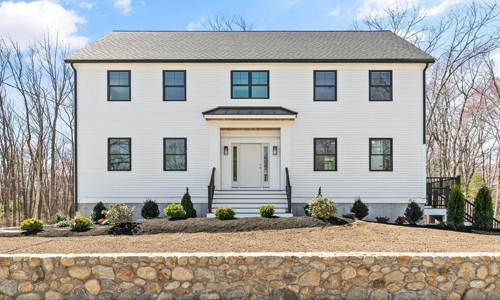 Four bedroom colonial style home in Reading, MA - exterior of home shown - white with eight windows and a double window above the white door in the center