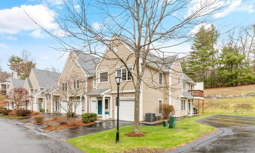 Two bedroom corner unit condo in North Reading, MA - exterior of home shown - tan with white trim and covered green door on the front