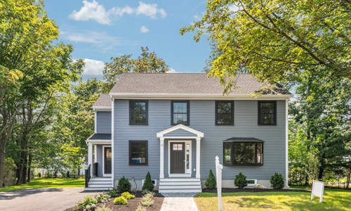 Slate blue colonial style home with double entrances both with dark doors; the house has both dark and white trim, a stone path and is surrounded by trees