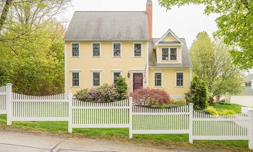 Detached Yellow Colonial surrounded by beautiful landscaping and a white fence