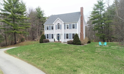 4 bedroom grey colonial style home with blue shutters set back from the road and surrounded by trees