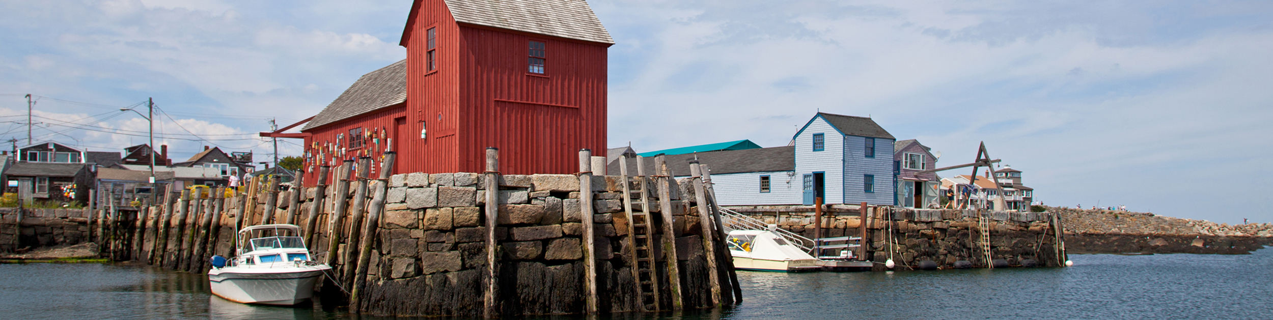 view of Motif One - a little red shack building on the water in Rockport MA