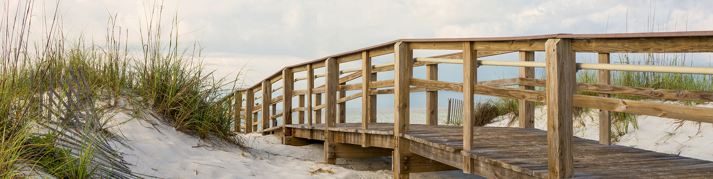 view of wooden walkway over sandy beach