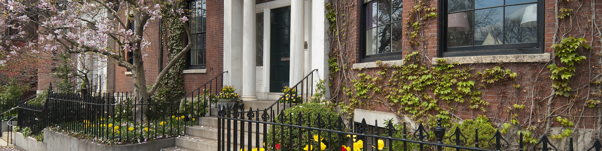 grand entranceway to residential building in Boston MA with rod iron fencing