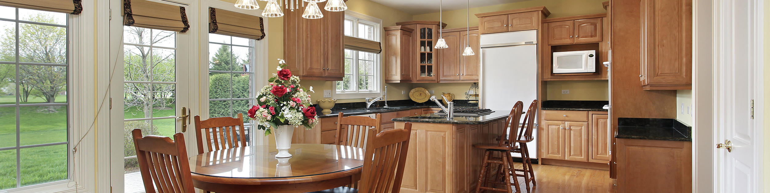 kitchen with light cabinets, dark granite and white appliances - also a kitchen table with a large vase of flowers