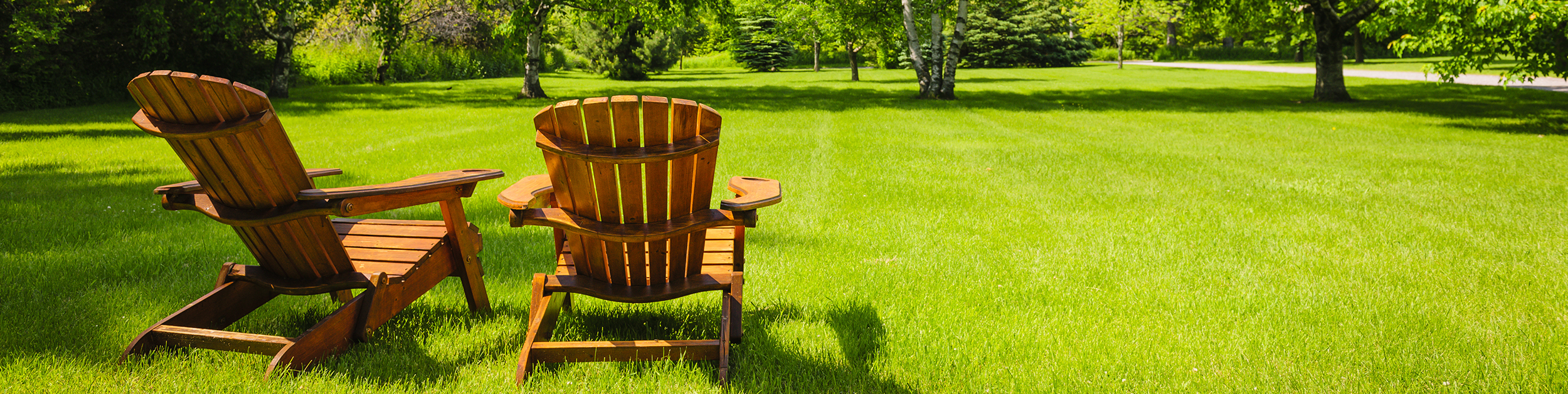view of two Adirondack chairs on a beautiful lawn