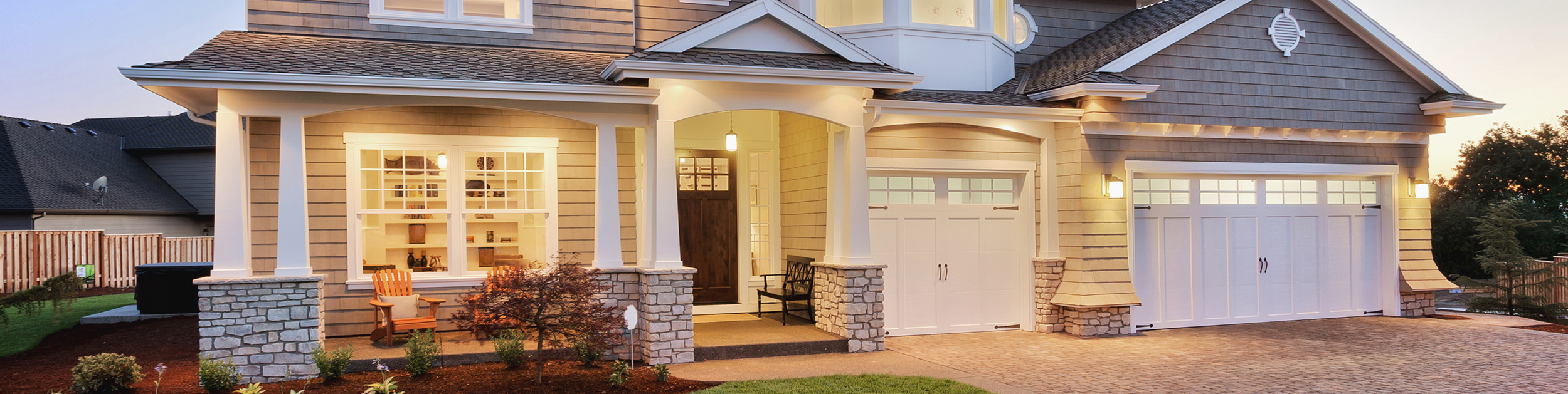 exterior of beautifully lit up home with a stone driveway - gray shingles with white trim and garage doors, stonework and pillars supporting the overhang with two adirondack chairs and a bench on the front porch