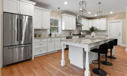 condo unit in a multi-family home in Newton MA - interior view of a fully remodeled kitchen is shown with white cabinets, an island and stainless steel appliances