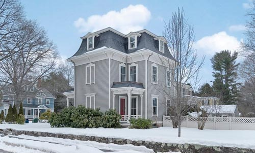 gray and white victorian style home in Newton MA with red door and fenced in yard