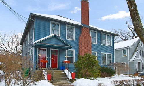 multi family home in Newton MA - blue with two red doors, cement stairs and brick chimney