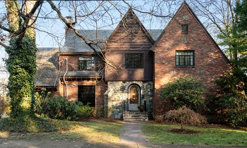 detached brown tudor style home in Newton MA - brick and stone is seen on the front with double peaks