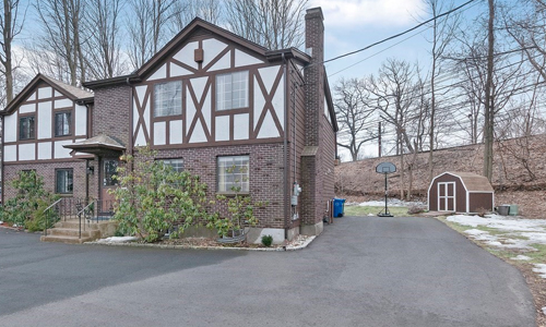 side by side condo made of wood and brick - tan and beige with large driveway and storage shed