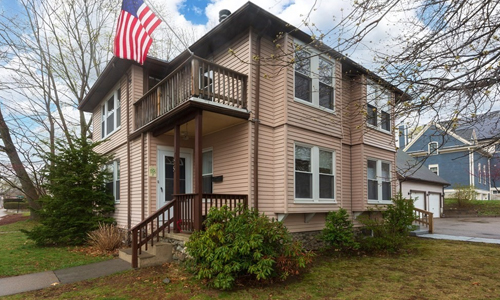 two story house - tan with brown trim and porches on both levels; an American flag is on the second floor porch