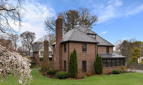 detached colonial style home in Newton MA - brick exterior with large chimney on the left and a glass enclosed room on the right