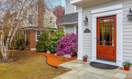front entrance of home shown - light gray with white trim and a wooden door  - there are potted plants and lights on both sides of the door, a flagstone patio style area leading to the door and beautiful shrubs and mulch along the front