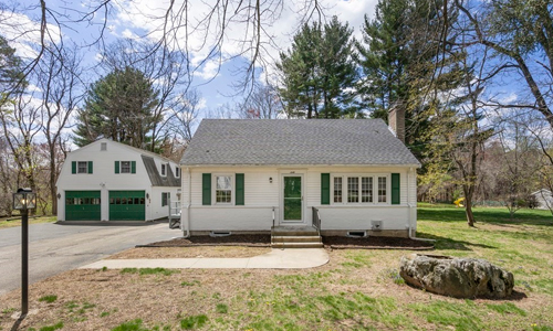 three bedroom cape style home - exterior of home is white with green door and shutters and a separate barn style garage with two green doors