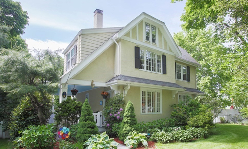 cream colored colonial style home with dark shutters and lovely shrubs and plantings out front