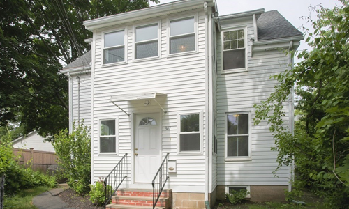 three bedroom colonial style home - white with brick steps and rod iron rail leading to white door