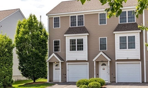 exterior of multi unit town home tan with white trim and doors