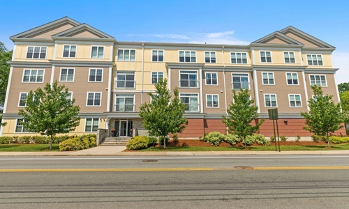 large two toned condominium building with lots of windows, peaks and one main entrance