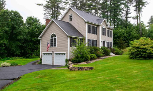 Tan colonial with dark shutters, 2 car garage, lots of shrubs, retaining wall and US flag