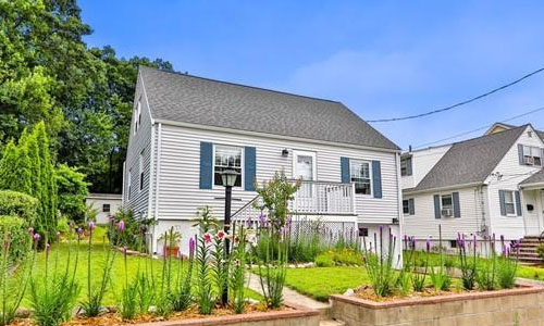 Exterior image of Detached Cape shown - gray with blue shutters, retainer wall with plantings out front