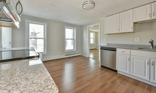 beautiful kitchen shown with white cabinets, hard wood floors and stainless steel appliances