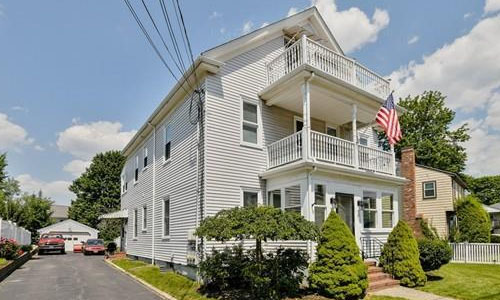 exterior of multi-level home shown - white with front porches and American flag