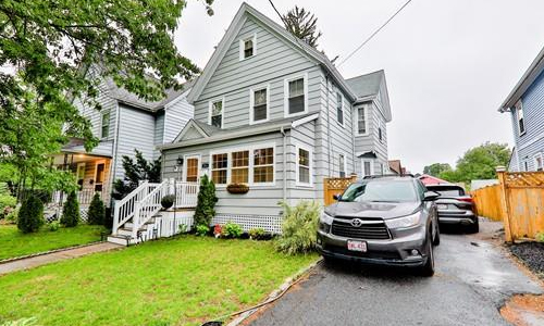 Exterior image of Detached Grey Colonial with vehicles shown in driveway