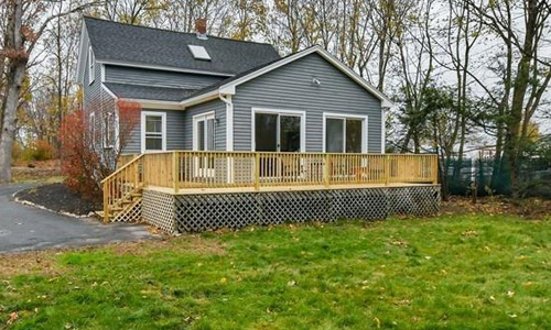 Detached Blue Colonial for sale in Mansfield, MA - exterior of home shown, back yard and deck are in view