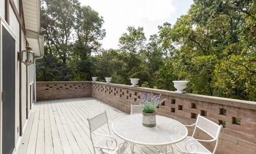 Four bedroom detached white contemporary ranch for sale in North Attleboro, MA - view of deck overlooking trees shown