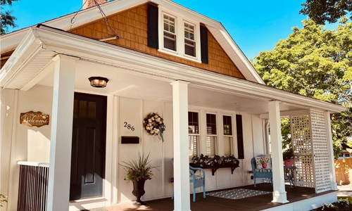 Three bedroom farmhouse, bungalow for sale in Boston, MA - exterior of home shown - white with black door and farmer's porch with pillars