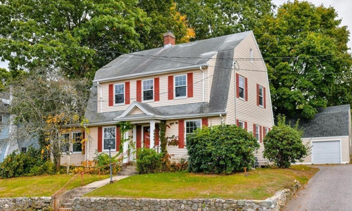 Four bedroom colonial for sale in Dedham, MA - exterior of home shown, tan with red shutters