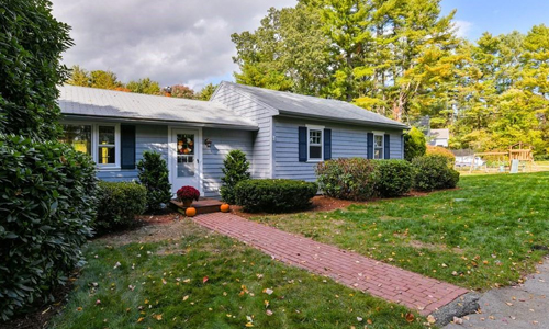 Three bedroom detached green ranch for sale in Norfolk, MA - exterior of home shown, home has brick walkway leading to white door with mums and pumpkins