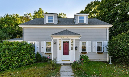 Two bedroom colonial for sale in Dedham, MA - exterior of home shown, gray with white trim and shutters - a stone walkway leads to a red door