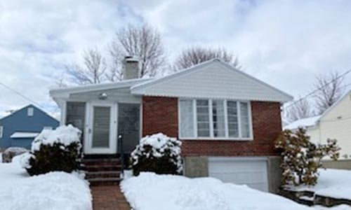 snow covered three bedroom ranch for sale in Milton, MA - partial brick front with white vinyl siding, brick walkway