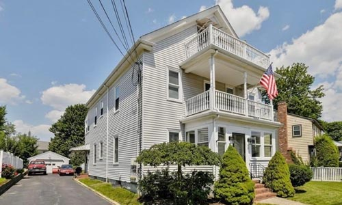 Multi family home in Dedham, MA - tan with white trim, brick stairs and three porches on the front
