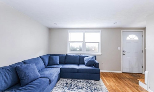 interior view of apartment for rent in Dedham MA - family room with hardwood floors, gray walls with white trim on double window, white door.  A large blue sectional couch and blue and white area rug are in the room.