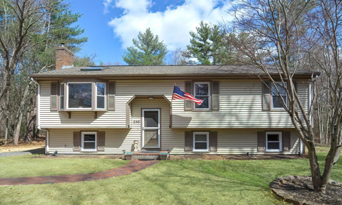 3 bedroom Ranch style home in Mansfield, MA - tan with brown shutters and an American flag out front