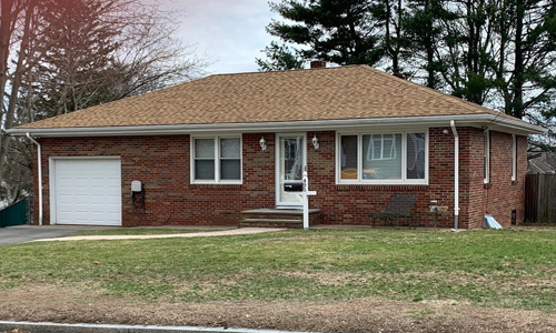 Two bedroom ranch style home in Woonsocket, RI - exterior of home shown - brick with white trim and garage door