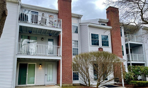 2 bedroom garden style condo in Natick, MA - exterior of multi level building shown - light gray with brick chimneys, balconies and white trim