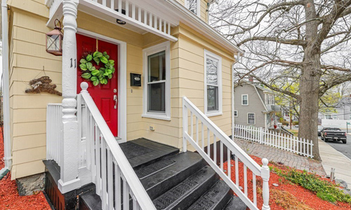 3 bedroom Colonial style home for sale in Boston, MA - light yellow with red door with decorative wreath, white trim and railings shown around dark colored stairs