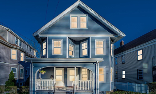 Multi level multi family home in Boston, MA - blue with white trim; surrounded by blue sky and another home on each site - all lights inside are lit and there is a covered porch out front
