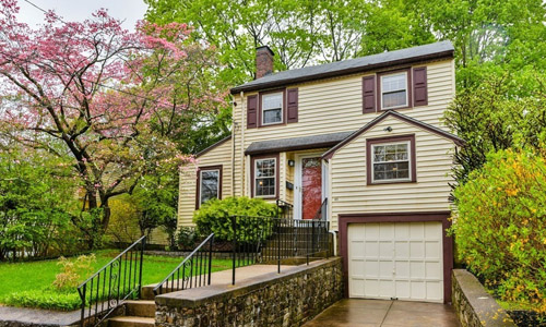3 bedroom Colonial style home for sale in Boston, MA - tan with darker brown shutters, red door to house and white garage door surrounded by Spring trees in the background and a stone wall, walkway and stairs out front