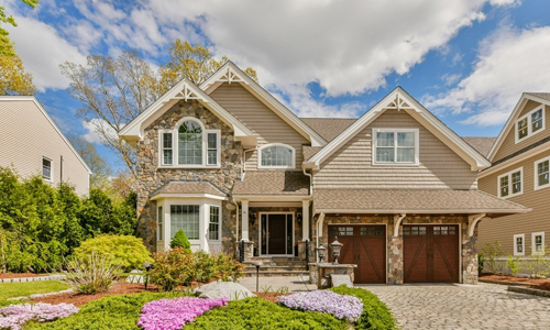 Tan colonial style home with partial stone front, two wooden garage doors, mulitple peaks, a bow window, a palladium window and beautiful landscape out front