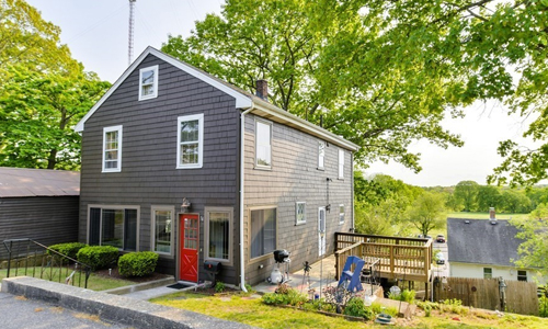 Brown colonial style home with red door, white trim and a deck on the right side