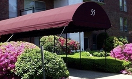 Exterior view of brick front multi unit condominium building; a large burgandy awning covers the stone path and has the number 55 on it.