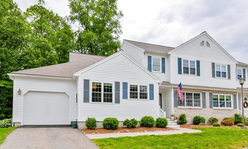 White colonial style home with blue shutters and an American flag out front