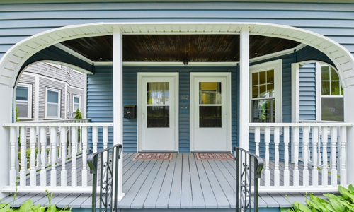 Double entrance of home with two white doors shown through an arched porch - home is blue with white trim and light gray flooring on the porch.